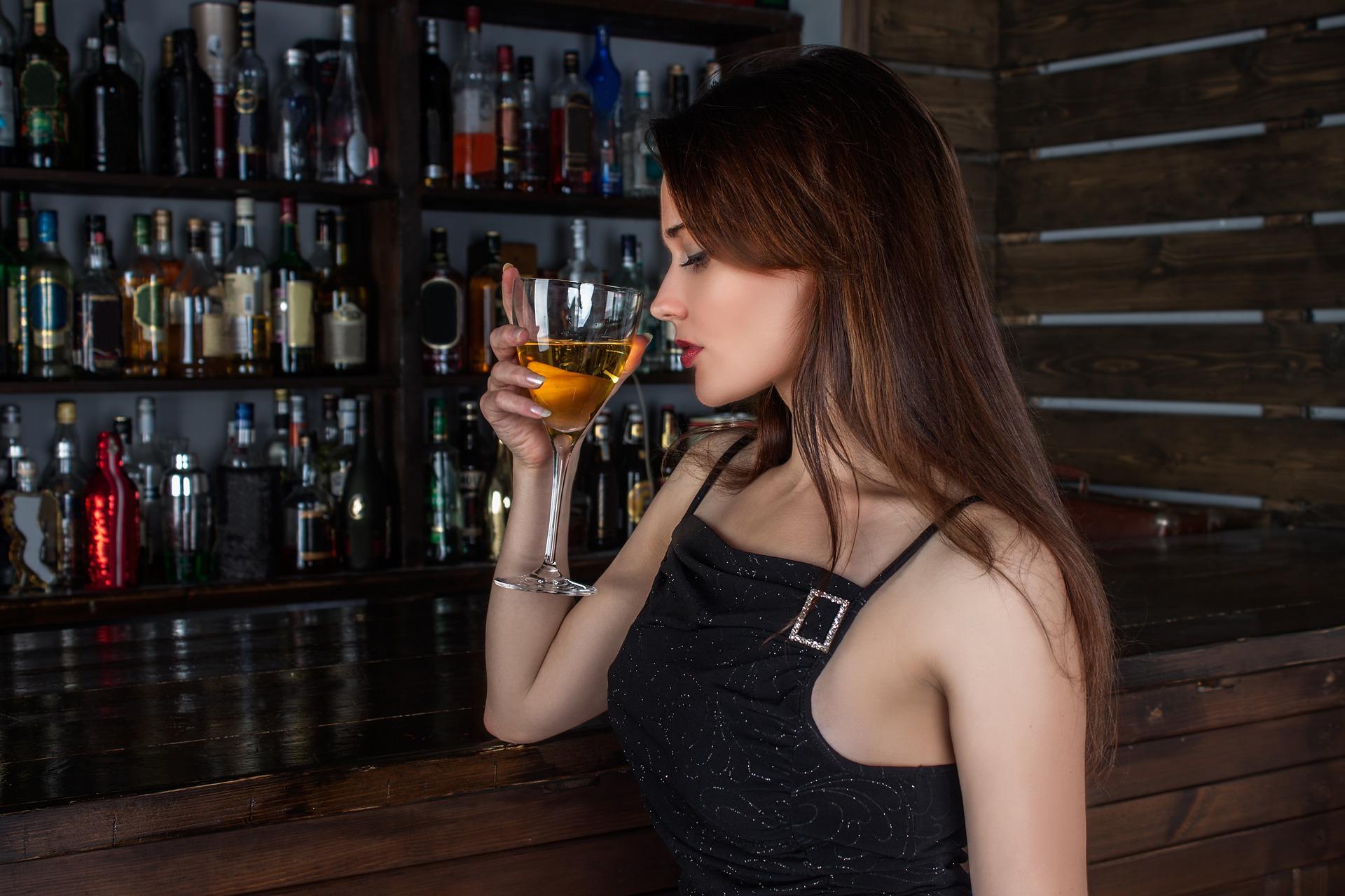 Девушка в баре с бокалом вина.